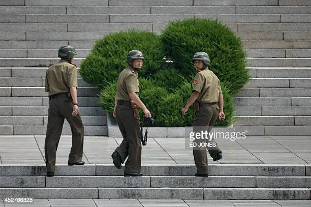 North Korean soldiers walk up the stairs to the Panmungak building opposite the military demarcation line seperating North and South Korea within the...