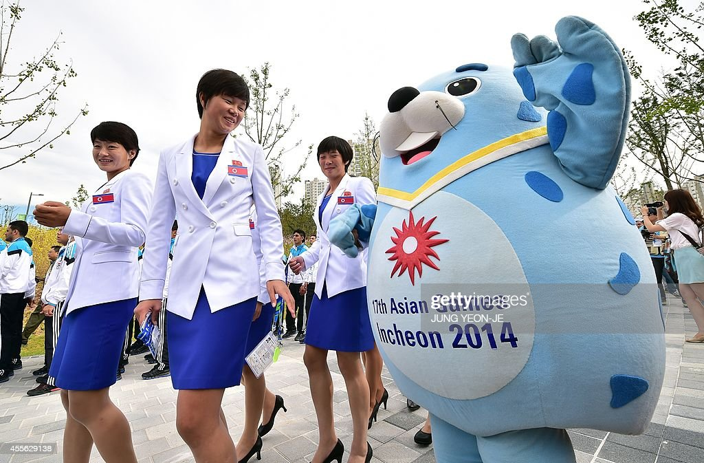 North Korean team members attend a welcome ceremony as a mascot greets them at the athletes village of the 2014 Asian Games in Incheon on September...