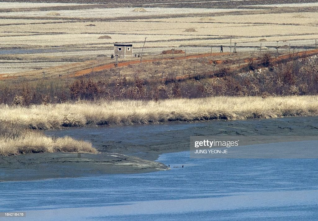 A North Korean (R) walks near a guard post in the propaganda village of Gijeongdong as seen from a South Korean observatory post in the border city of Paju near the Demilitarized Zone (DMZ) dividing the two Koreas on March 21, 2013. North Korea issued an air raid warning and put its military on alert on March 21, South Korea's Unification Ministry said, in what appeared to be a drill at a time of heightened tensions.