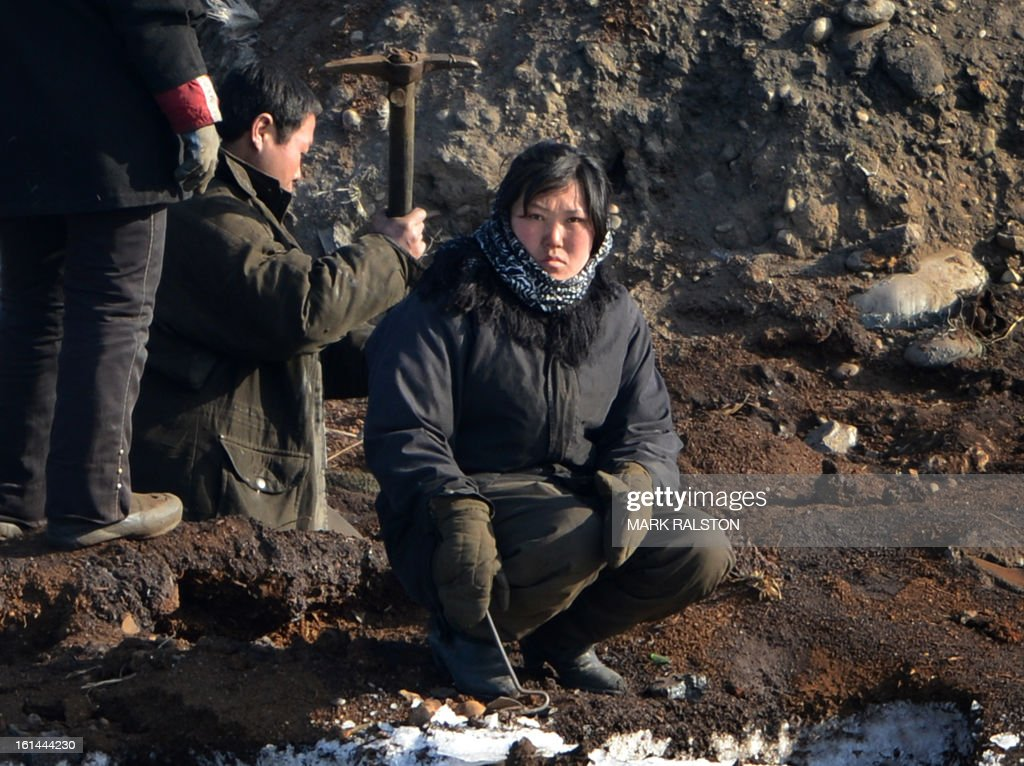 A North Korean women stops to watch a Chinese boat pass by as other workers dig in freezing temperatures on the banks of the Yalu River at the North Korean town of Sinuiju on February 11, 2013 across from the Chinese city of Dandong. A North Korean state media outlet has accused the United States of 'jumping to conclusions' that the North would soon stage a nuclear test, adding to the confusion over its immediate intentions. The US and its ally South Korea are 'fussing over speculation' without knowing exactly what action the North plans to take, Tongil Sinbo, a Japan-based pro-North weekly magazine funded by Pyongyang, said. AFP PHOTO/Mark RALSTON