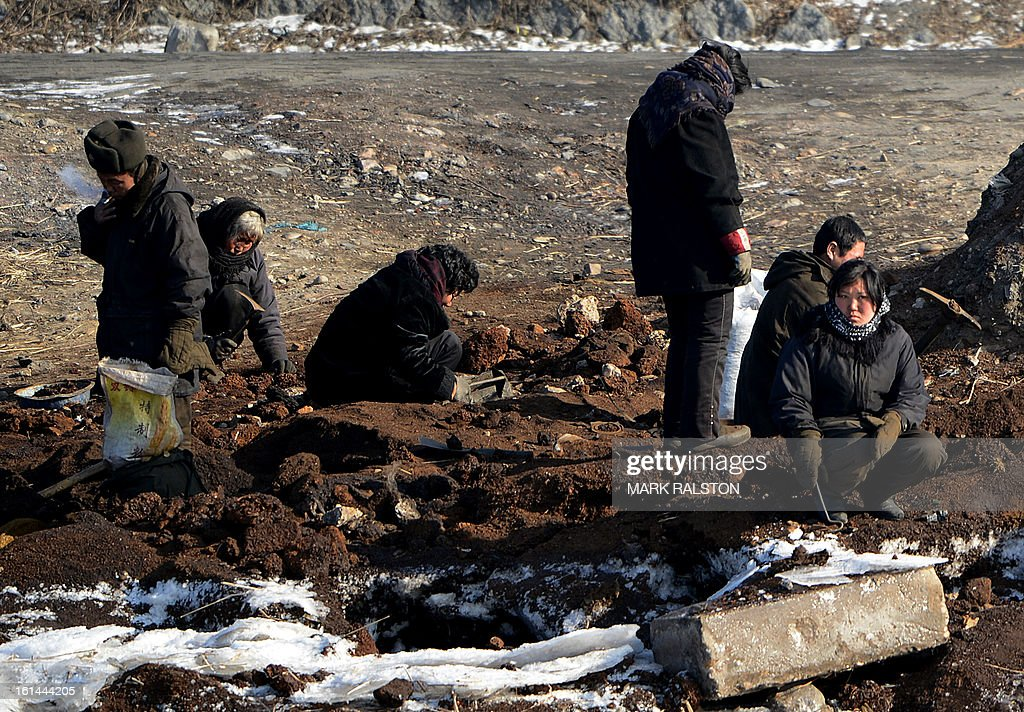 North Korean workers dig in freezing temperatures on the banks of the Yalu River at the North Korean town of Sinuiju on February 11, 2013 across from the Chinese city of Dandong. A North Korean state media outlet has accused the United States of 'jumping to conclusions' that the North would soon stage a nuclear test, adding to the confusion over its immediate intentions. The US and its ally South Korea are 'fussing over speculation' without knowing exactly what action the North plans to take, Tongil Sinbo, a Japan-based pro-North weekly magazine funded by Pyongyang, said. AFP PHOTO/Mark RALSTON