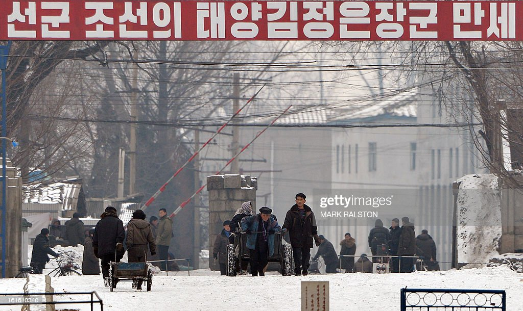 North Korean workers pass beneath a banner saying 'The Great General Kim Jong-Un' at the North Korean town of Sinuiju across from the Chinese city of Dandong, on February 13, 2013. While the rest of the world reacted with outrage, North Koreans were swept up in a 'storm of excitement' over their country's latest nuclear test, state media reported. The countries third nuclear test was widely condemned by the international community, led by the United States and the UN Security Council, which met in emergency session the same day. AFP PHOTO/Mark RALSTON