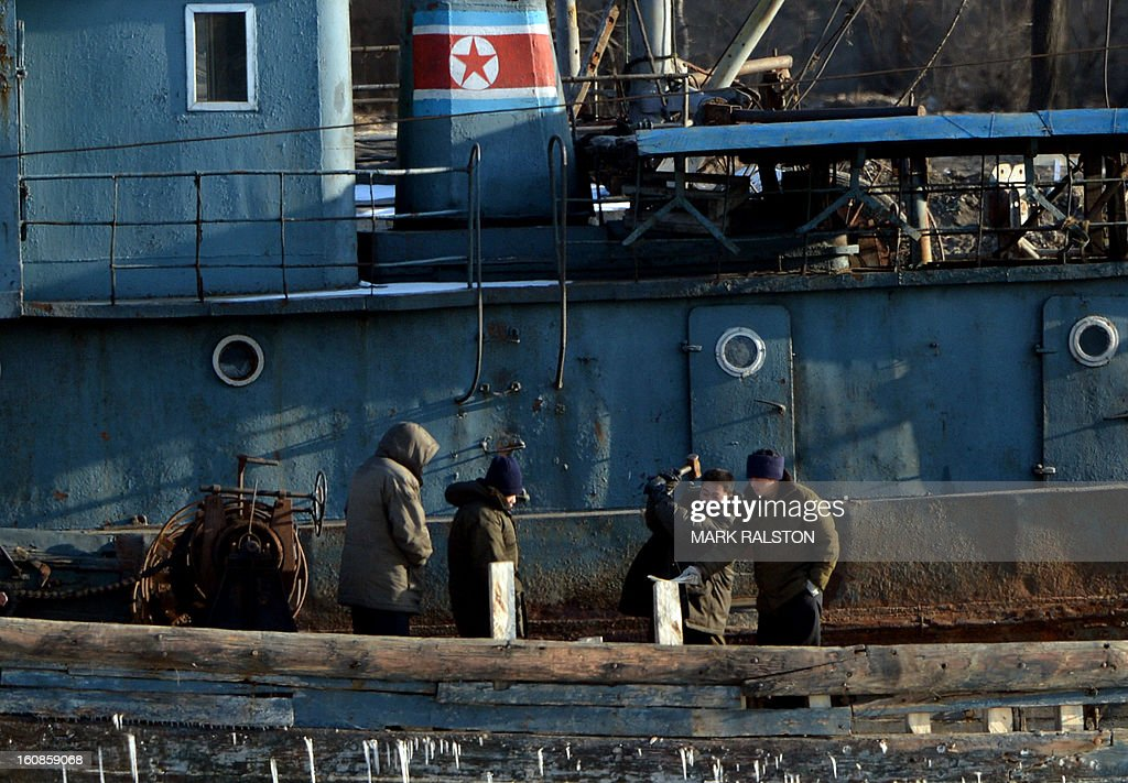 North Korean workers repair a barge beside a patrol boat on the Yalu River near the town of Sinuiju on February 7, 2013 across from the Chinese city of Dandong. North Korea has vowed to carry out a third nuclear test, but scientists and concerned foreign governments may have a tough time verifying the actions of the reclusive state. AFP PHOTO/Mark RALSTON