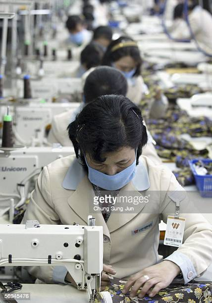 North Korean workers sew at the assembly line of the factory of textile company Shinwon Inc at the Kaesong industrial complex on February 27 2006 in...