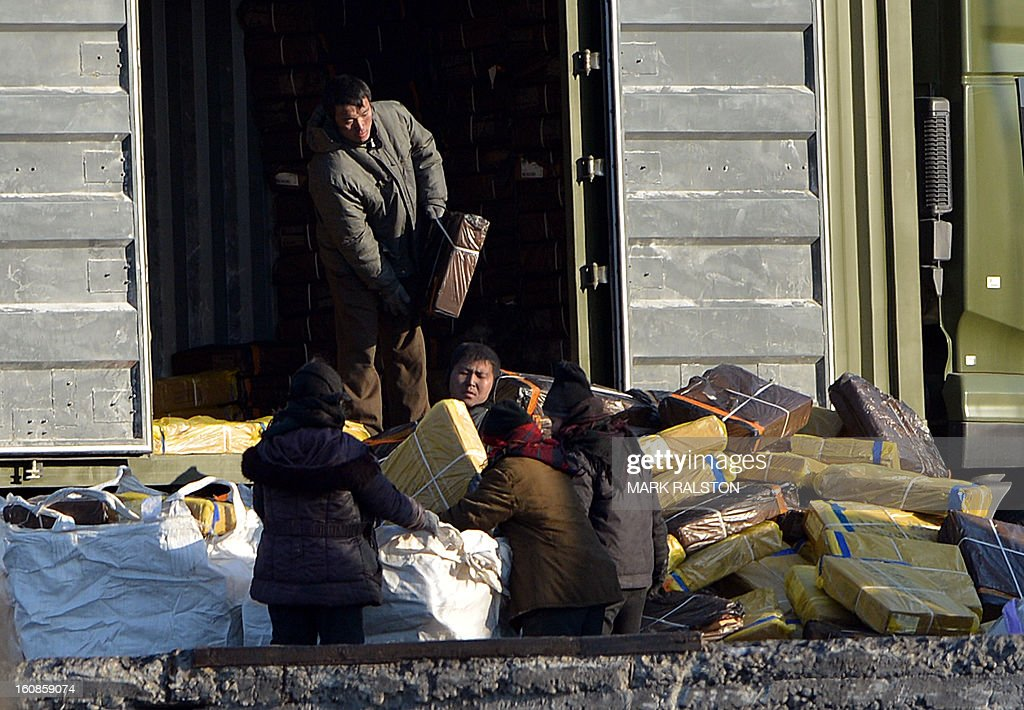 North Korean workers unload a truck on the banks of the Yalu River near the town of Sinuiju on February 7, 2013 across from the Chinese city of Dandong. North Korea has vowed to carry out a third nuclear test, but scientists and concerned foreign governments may have a tough time verifying the actions of the reclusive state. AFP PHOTO/Mark RALSTON