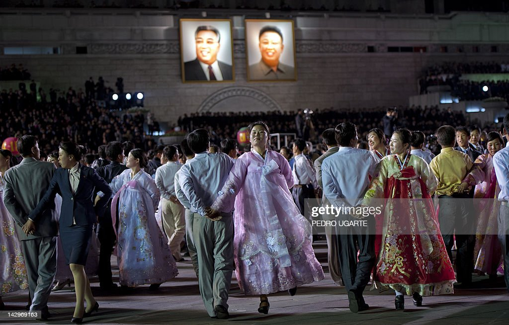North Koreans dance in front of portraits of North Korean late president Kim Il-Sung (L) and his son Kim Jung-Il during celebrations to mark the 100th birth anniversary of the country's founding leader Kim Il-Sung, in Pyongyang on April 16, 2012. The commemorations came just three days after a satellite launch timed to mark the centenary fizzled out embarrassingly when the rocket apparently exploded within minutes of blastoff and plunged into the sea.