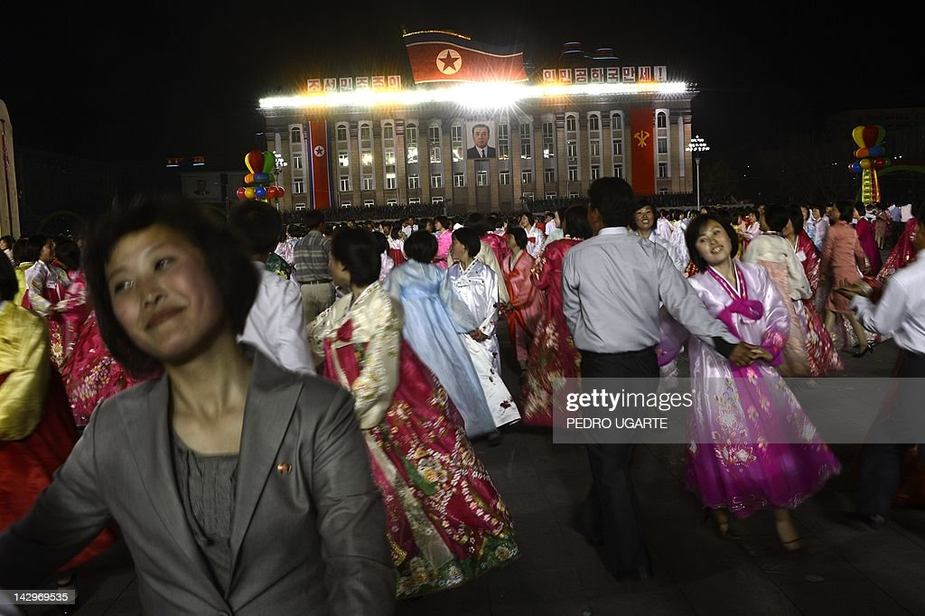 North Koreans performers dance in front of portraits of North Korean late president Kim Il-Sung (L) and his son Kim Jung-Il during celebrations to mark the 100th birth anniversary of the country's founding leader Kim Il-Sung, in Pyongyang on April 16, 2012. The commemorations came just three days after a satellite launch timed to mark the centenary fizzled out embarrassingly when the rocket apparently exploded within minutes of blastoff and plunged into the sea.