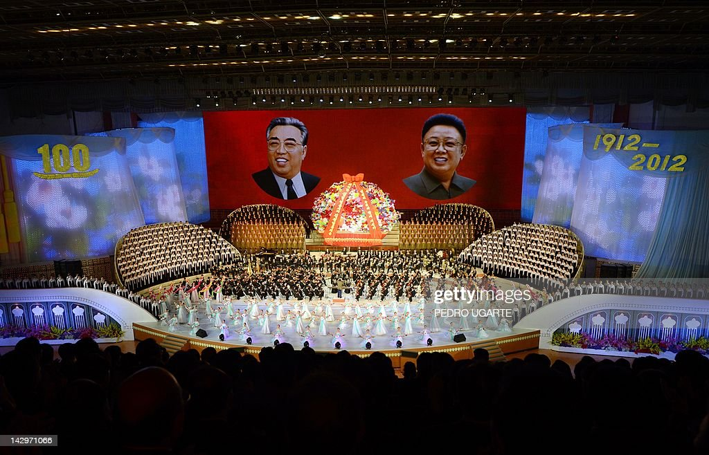 North Koreans performers sing in front of portraits of founding president Kim Il-Sung (L) and his son Kim Jong-Il during celebrations to mark the 100th birth anniversary of the country's founding leader Kim Il-Sung, in Pyongyang on April 16, 2012. The commemorations came just three days after a satellite launch timed to mark the centenary fizzled out embarrassingly when the rocket apparently exploded within minutes of blastoff and plunged into the sea.