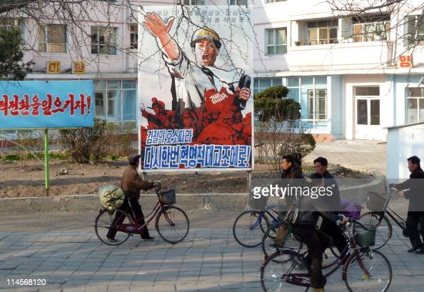 North Koreans push their bicycles past a propaganda poster on a street in Kaesong North Hwanghae Province close to the border with South Korea in...