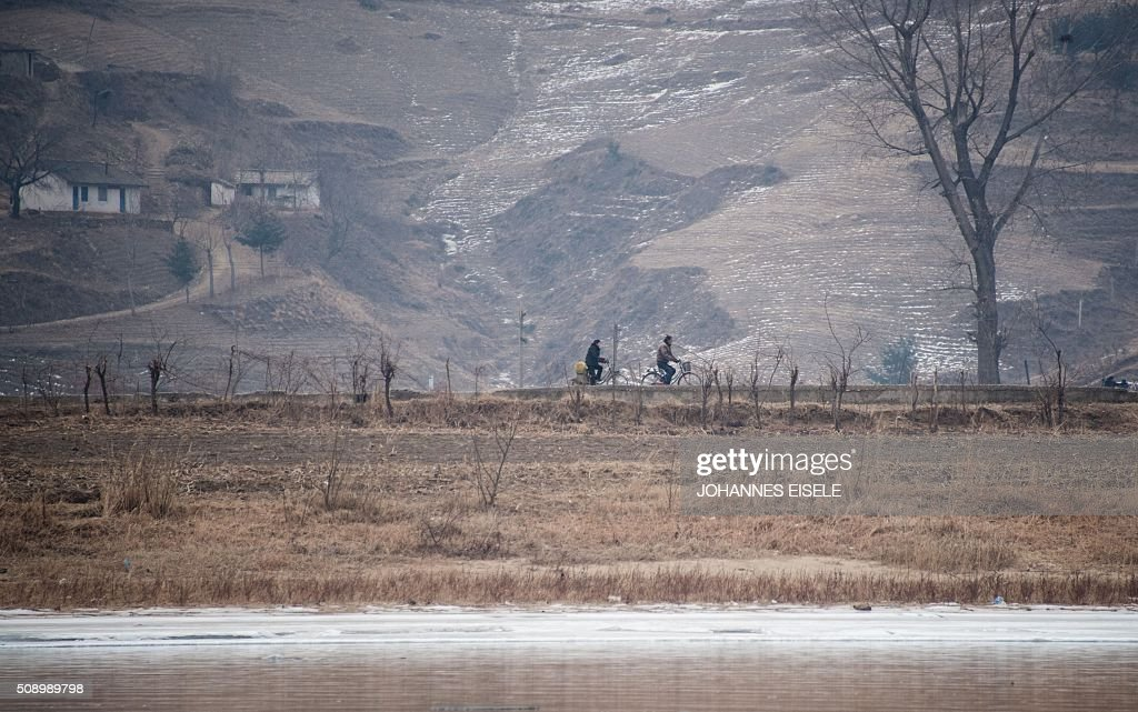 North Koreans ride their bicycles along the banks of the Yalu River in the North Korean town of Sinuiju, in an image taken from across the river in the Chinese border town of Dandong on February 8, 2016. The UN Security Council strongly condemned North Korea's rocket launch on February 7 and agreed to move quickly to impose new sanctions that will punish Pyongyang for 'these dangerous and serious violations.' With backing from China, Pyongyang's ally, the council again called for 'significant measures' during an emergency meeting held after North Korea said it had put a satellite into orbit with a rocket launch. AFP PHOTO / JOHANNES EISELE / AFP / JOHANNES EISELE
