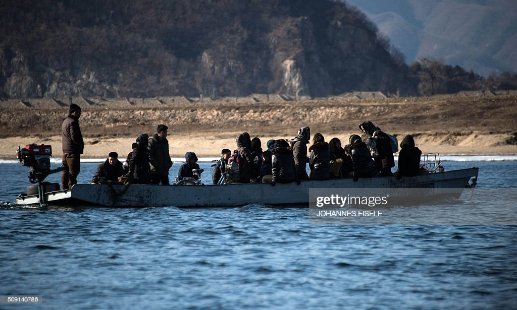 North Koreans sit inside a boat on the Yalu River near the North Korean town of Sinuiju, as seen from across the river from the Chinese border town of Dandong on February 9, 2016. The rocket launched by North Korea at the weekend seemed more powerful than its 2012 predecessor, but Pyongyang still lacks the expertise to transform it into a ballistic missile capable of reaching the US mainland, South Korean officials said on February 9. AFP PHOTO / JOHANNES EISELE / AFP / JOHANNES EISELE