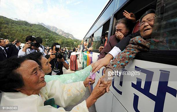 North Koreans take the hands of their departing South Korean family members as they bid farewell following their threeday family reunion at the North...