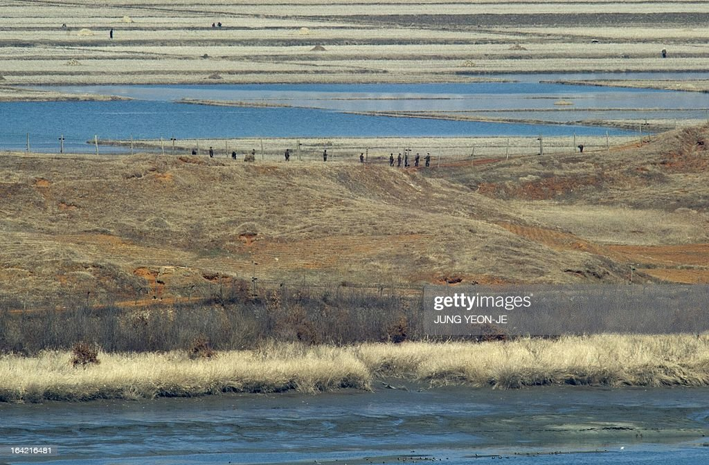 North Koreans (C) walk along a military fence in the propaganda village of Gijeongdong as seen from a South Korean observatory post in the border city of Paju near the Demilitarized Zone (DMZ) dividing the two Koreas on March 21, 2013. North Korea issued an air raid warning and put its military on alert on March 21, South Korea's Unification Ministry said, in what appeared to be a drill at a time of heightened tensions.