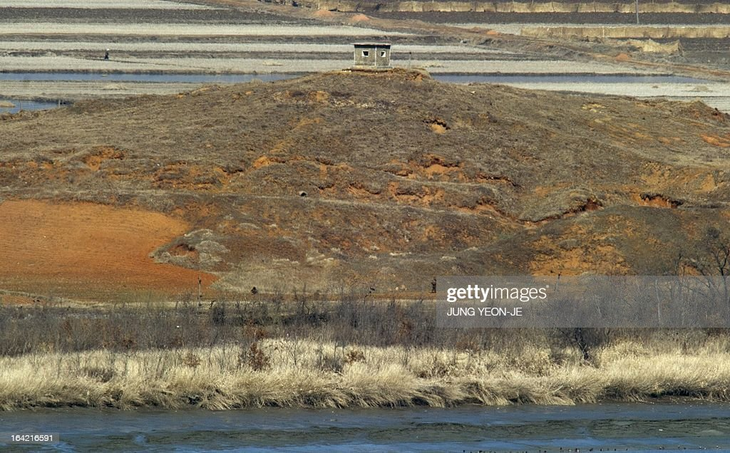 North Koreans (bottom) walk along a military fence in the propaganda village of Gijeongdong as seen from a South Korean observatory post in the border city of Paju near the Demilitarized Zone (DMZ) dividing the two Koreas on March 21, 2013. North Korea issued an air raid warning and put its military on alert on March 21, South Korea's Unification Ministry said, in what appeared to be a drill at a time of heightened tensions.