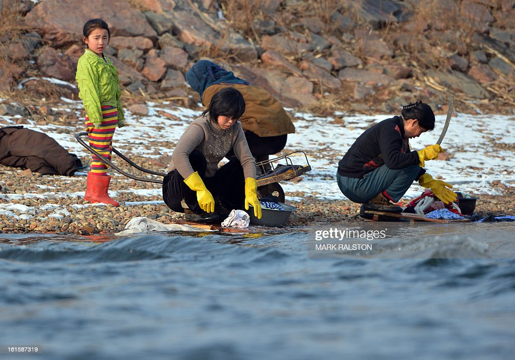 North Korean's wash clothing in the Yalu River near the North Korean town of Sinuiju after the country conducted it's third nuclear test on February 12, 2013 across from the Chinese city of Dandong. North Korea staged its most powerful nuclear test yet on February 12, claiming a breakthrough with a 'miniaturised' device in a striking act of defiance to global powers including its sole patron China. AFP PHOTO/Mark RALSTON