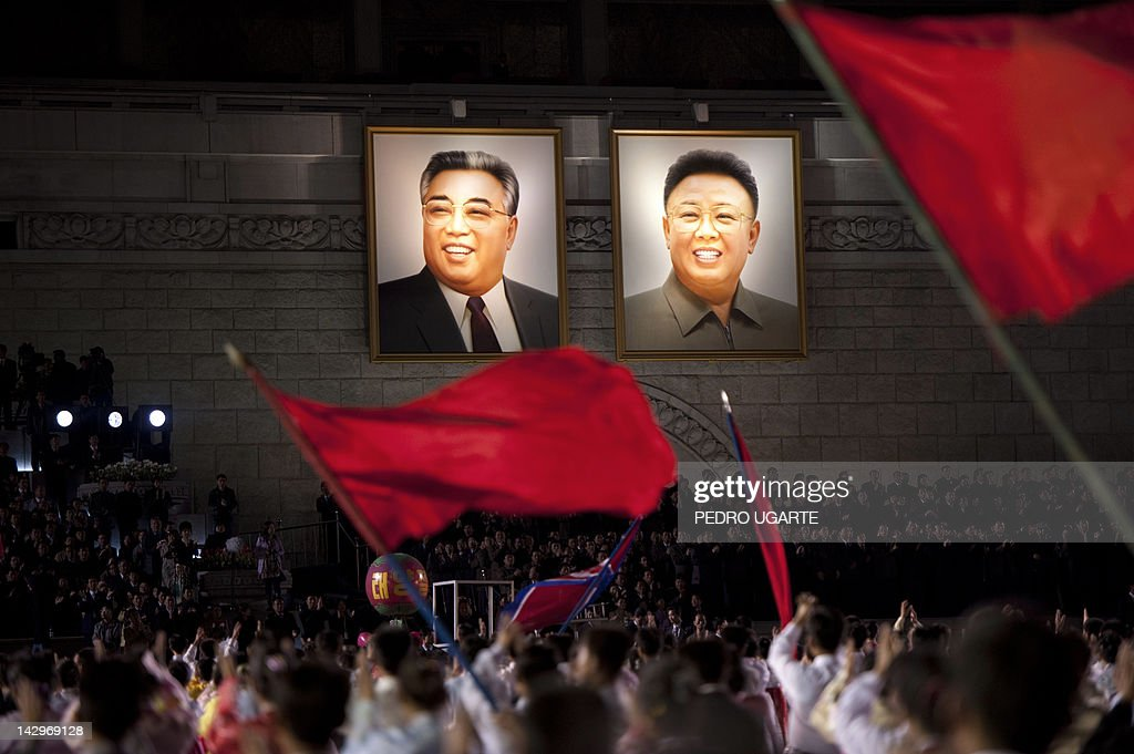 North Koreans wave flags in front of portraits of North Korean late president Kim Il-Sung (L) and his son Kim Jung-Il during celebrations to mark the 100th birth anniversary of the country's founding leader Kim Il-Sung, in Pyongyang on April 16, 2012. The commemorations came just three days after a satellite launch timed to mark the centenary fizzled out embarrassingly when the rocket apparently exploded within minutes of blastoff and plunged into the sea.