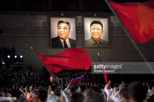 North Koreans wave flags in front of portraits of North Korean late president Kim IlSung and his son Kim JungIl during celebrations to mark the 100th...