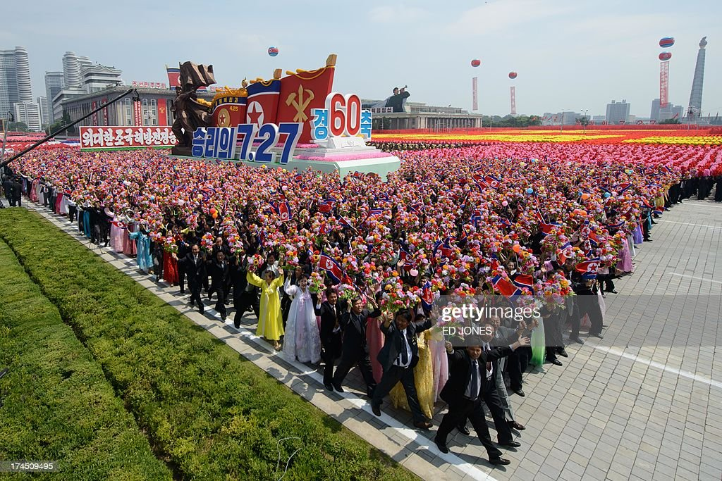 North Koreans wave flowers as they take part in a military parade past Kim Il-Sung square marking the 60th anniversary of the Korean war armistice in Pyongyang on July 27, 2013. North Korea mounted its largest ever military parade on July 27 to mark the 60th anniversary of the armistice that ended fighting in the Korean War, displaying its long-range missiles at a ceremony presided over by leader Kim Jong-Un. AFP PHOTO / Ed Jones