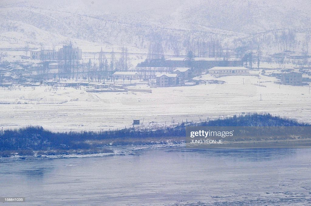 North Korea's border county of Kaepoong covered with snow is seen from a South Korean observation post in Paju near the Demilitarized Zone (DMZ) dividing the two Koreas on January 1, 2013. North Korean leader Kim Jong-Un called on January 1, 2013 for an easing of tensions with the South and flagged a 'radical turnabout' in the national economy in a rare voiced message broadcast on state television. AFP PHOTO / JUNG YEON-JE