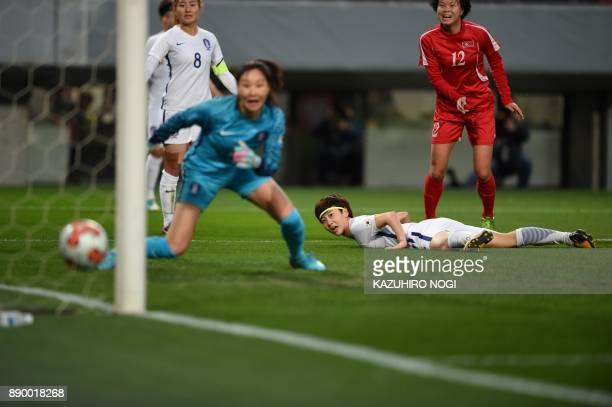 North Korea's forward Kim Yun Mi scores a goal past South Korea's goalkeeper Kim Jungmi during the women's football match between North Korea and...