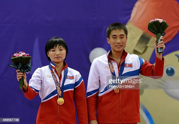 North Korea's gold medalists Kim Jong and Kim Hyokbong pose after the mixed doubles table tennis final at the 2014 Asian Games at the Suwon Gymnasium...