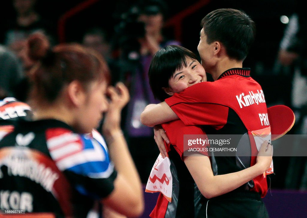 North Korea's Kim Hyok Bong (R) and Kim Jong (L) celebrate after winning against South Korea's Lee Sangsu and Park Youngsook in the Final match of the mixed doubles of the World Table Tennis Championships on May 18, 2013 in Paris. AFP PHOTO / Jacques DEMARTHON