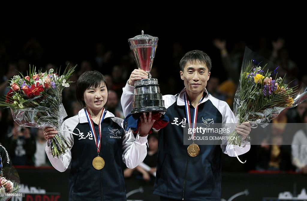 North Korea's Kim Hyok Bong (R) and Kim Jong (L) celebrate their mixed doubles title on the podium of the World Table Tennis Championships on May 18, 2013 in Paris. AFP PHOTO / Jacques DEMARTHON