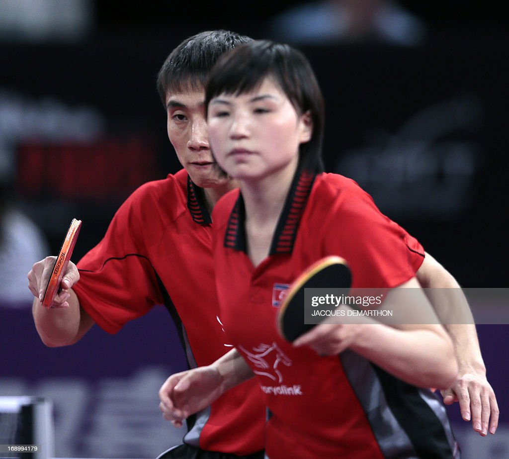 North Korea's Kim Hyok Bong (L) and Kim Jong (R) compete against South Korea's Lee Sangsu and Park Youngsook in the Final match of the mixed doubles of the World Table Tennis Championships on May 18, 2013 in Paris. North Korea won the title. AFP PHOTO / Jacques DEMARTHON