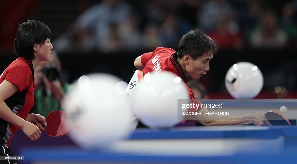 North Korea's Kim Hyok Bong (R) and Kim Jong (L) compete against South Korea's Lee Sangsu and Park Youngsook in the Final match of the mixed doubles of the World Table Tennis Championships on May 18, 2013 in Paris. North Korea won the title. AFP PHOTO / Jacques DEMARTHON
