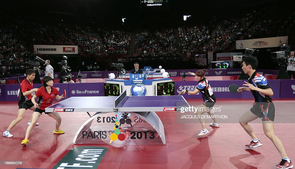 North Korea's Kim Hyok Bong (L) and Kim Jong (2nd L) compete against South Korea's Lee Sangsu (R) and Park Youngsook (2nd R) in the final match of the mixed doubles of the World Table Tennis Championships on May 18, 2013 in Paris. North Korea won the title. AFP PHOTO / Jacques DEMARTHON