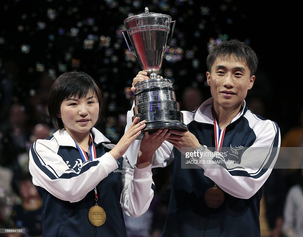 North Korea's Kim Hyok Bong (R) and Kim Jong (L) hold their trophy as they celebrate their mixed doubles title on the podium of the World Table Tennis Championships on May 18, 2013 in Paris. AFP PHOTO / Jacques DEMARTHON