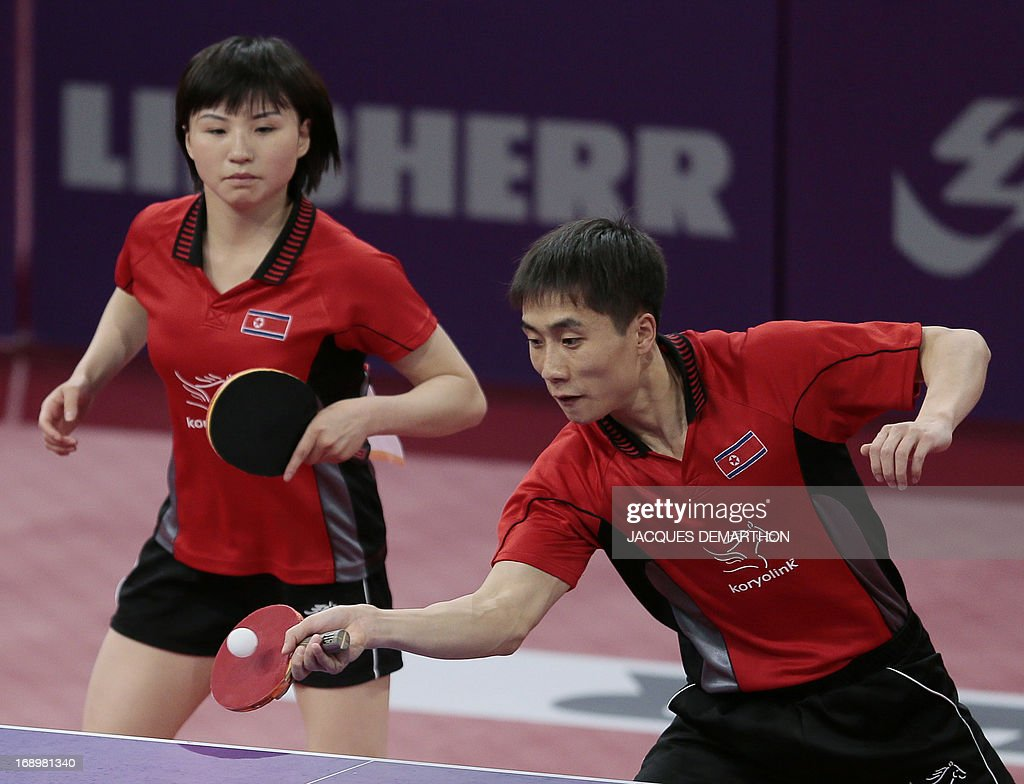 North Korea's Kim Hyok Bong (R) and Kim Jong play against (unseen) Hong Kong's Cheung Yuk and Jiang Huajun on May 18, 2013 in Paris, during their mixed double semi-final at the World Table Tennis Championships.