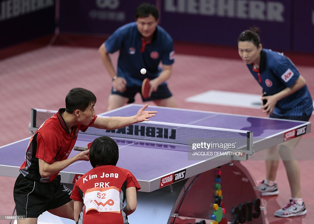 North Korea's Kim Hyok Bong (L, back) and Kim Jong serve to Hong Kong's Cheung Yuk and Jiang Huajun on May 18, 2013 in Paris , during their mixed double semi-final at the World Table Tennis Championships.