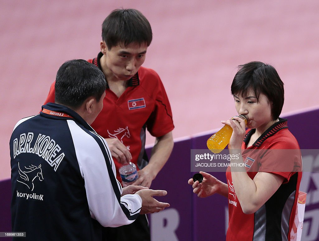 North Korea's Kim Hyok Bong (C) and Kim Jong (R) talk with their coach during a break in their match against (unseen) Hong Kong's Cheung Yuk and Jiang Huajun on May 18, 2013 in Paris , during their mixed double semi-final at the World Table Tennis Championships.