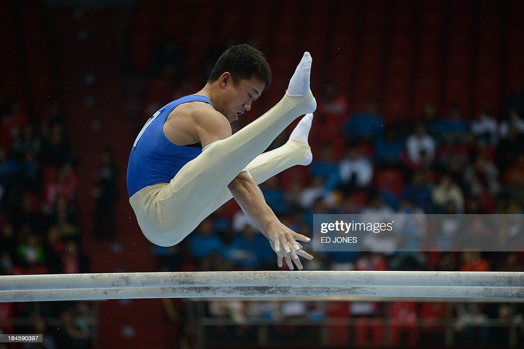 North Korea's Kim Kwang Chun competes in the Men's Parallel Bar final event of the 6th East Asian Games in Tianjin on October 14, 2013. The eastern Chinese city is hosting the East Asian Games which sees nine countries participating in 262 events across 22 different sports. AFP PHOTO / Ed Jones