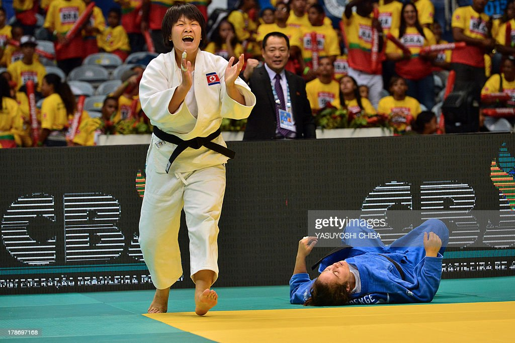 North Korea's Kyong Sol (white) reacts after winning against Catherine Roberge in a women's -78kg category semifinal, during the IJF World Judo Championship, in Rio de Janeiro, Brazil, on August 30, 2013. AFP PHOTO / YASUYOSHI CHIBA