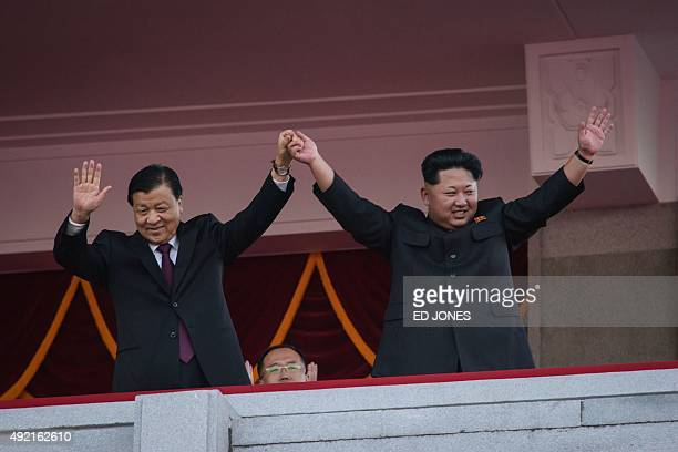 North Korea's leader Kim JongUn and Chinese Politburo standing committee member Liu Yunshan wave from a balcony towards participants of a mass...