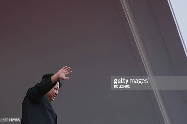 North Korea's leader Kim JongUn waves from a balcony towards participants of a mass military parade at Kim IlSung square in Pyongyang on October 10...