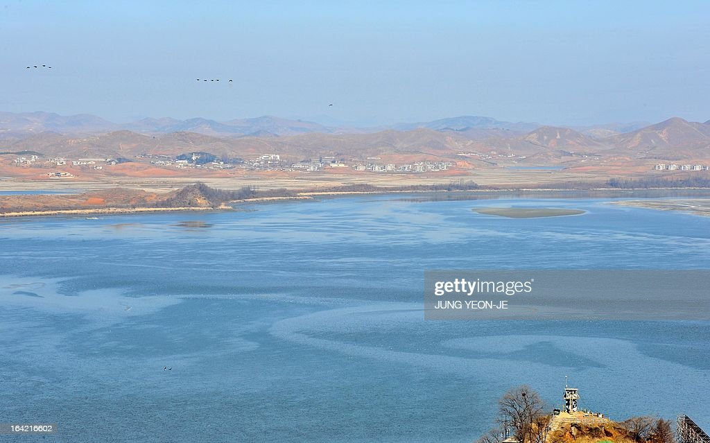North Korea's propaganda village of Gijeongdong (far) is seen from a South Korean observatory post in the border city of Paju near the Demilitarized Zone (DMZ) dividing the two Koreas on March 21, 2013. North Korea issued an air raid warning and put its military on alert on March 21, South Korea's Unification Ministry said, in what appeared to be a drill at a time of heightened tensions. AFP PHOTO / JUNG YEON-JE
