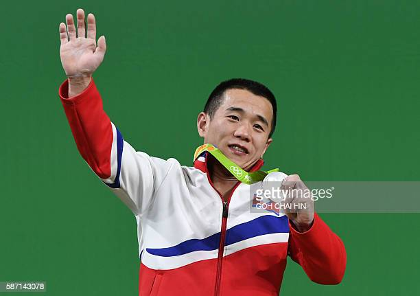North Korea's silver medallist Om Yun Chol waves during the men's 56kg weightlifting event at the Rio 2016 Olympic games in Rio de Janeiro on August...