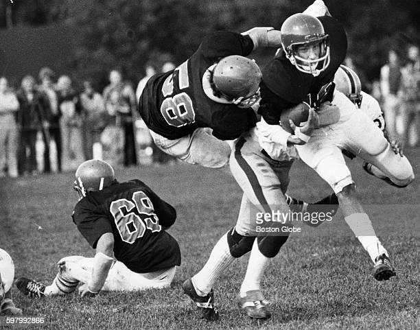 North Reading High School guard Doug Barnard back right throws North Andover quarterback Dave Walsh right down during a game and tosses North Andover...
