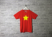 North Vietnam 1945 to1955 flag on shirt and hanging on the wall with brick pattern wallpaper, flag of Democratic Republic of Vietnam yellow star on red.