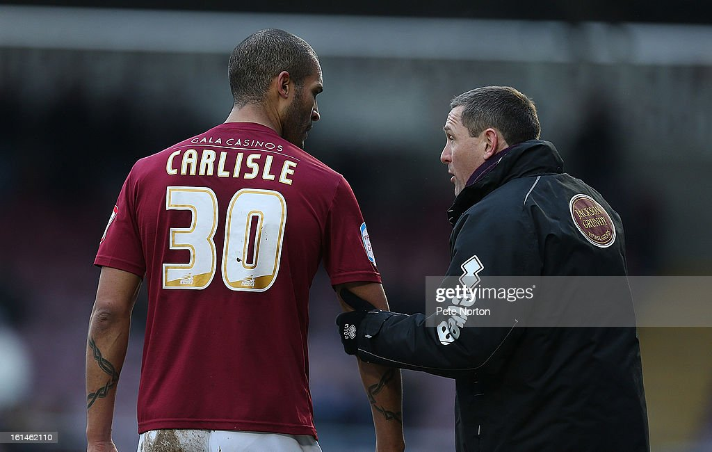 Northampotn Town manager Aidy Boothroyd gives instructions to <a gi-track='captionPersonalityLinkClicked' href=/galleries/search?phrase=Clarke+Carlisle&family=editorial&specificpeople=204318 ng-click='$event.stopPropagation()'>Clarke Carlisle</a> during the npower League Two match between Northampton Town and Rochdale at Sixfields Stadium on February 9, 2013 in Northampton, England.