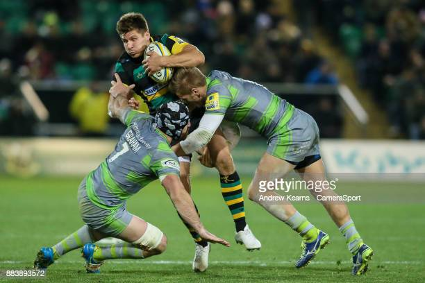 Northampton Saints' Piers Francis is tackled by Newcastle Falcons' Gary Graham and Chris Harris during the Aviva Premiership match between...