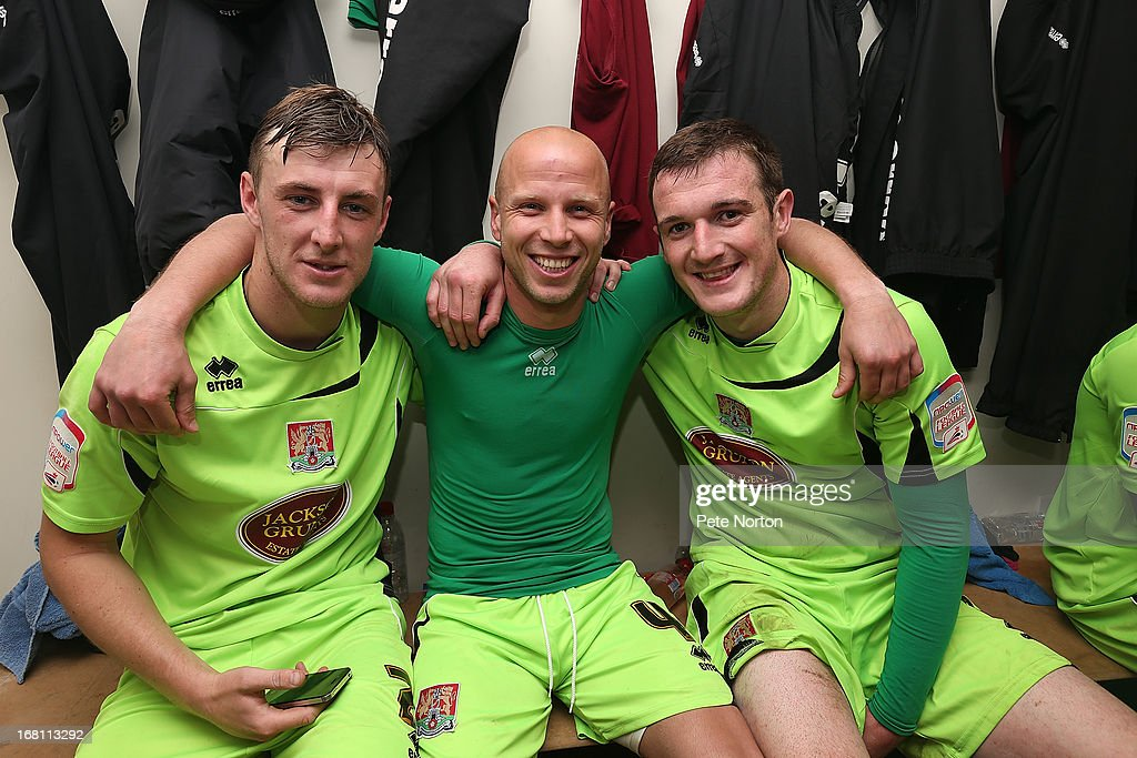 Northampton Town goal scorer Luke Guttridge (C) celebrates with team-mates Lee Collins and John Johnson in the changing room after the npower League Two Play Off Semi Final Second Leg between Cheltenham Town and Northampton Town at Abbey Business Stadium on May 5, 2013 in Cheltenham, England.