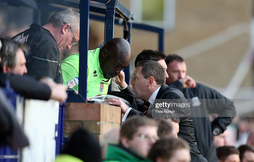 Northampton Town manager Aidy Boothroyd gives instructions to Adebayo Akinfenwa prior to him coming on as a substitute during the npower League Two match between Southend United and Northampton Town at Roots Hall on February 16, 2013 in Southend, England.