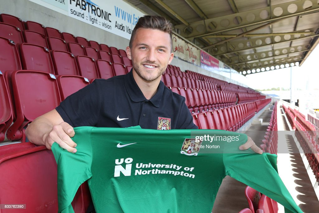 Northampton Town new signing Luke Coddington poses with a shirt during a photo call at Sixfields on August 17, 2017 in Northampton, England.