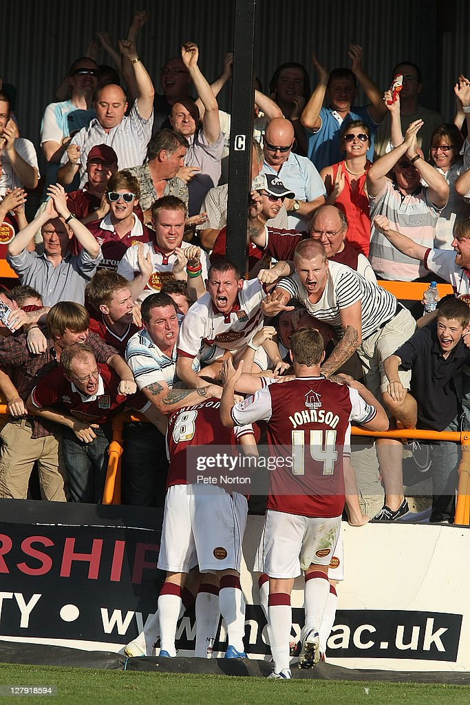 Northampton Town players and fans celebrate after Ben Tozer (hidden) had scored his sides second goal during the npower League two match between Barnet and Northampton Town at Underhill Stadium on October 1, 2011 in Barnet, England.