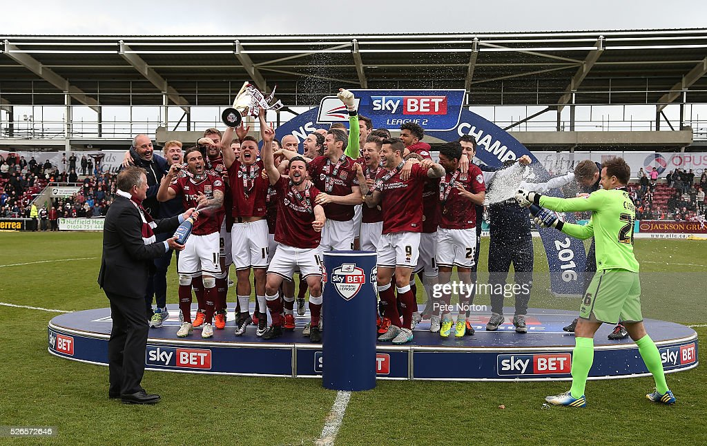 Northampton Town players celebrate after recieving the Sky Bet League Two champions trophy after Sky Bet League Two match between Northampton Town and Luton Town at Sixfields Stadium on April 30, 2016 in Northampton, England.