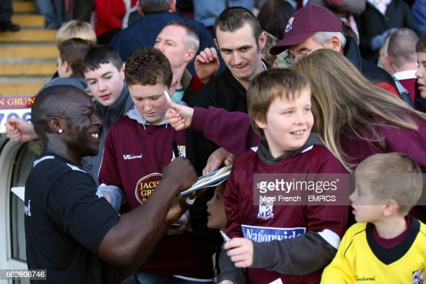 Northampton Town's Adebayo Akinfenwa signs autographs for supporters during the prematch warm up
